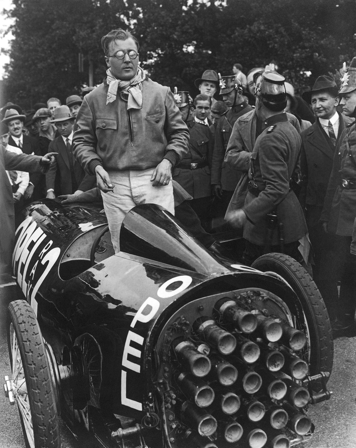 """Visionaries: Fritz von Opel in the RAK 2 and Otto Willi Gail, author of the book """"Mit Raketenkraft ins Weltenall – Vom Feuerwagen zum Raumschiff"""" (back right, with tie)."""