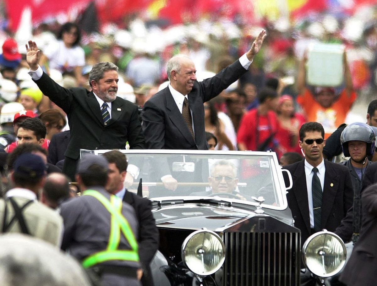 ** RETRANSMISSION OF DLMX107 FOR ALTERNATE CROP ** Brazilian President-elect Luiz Inacio Lula da Silva, left, and his vice-President Jose Alencar wave as they ride in an open car in Brasilia en route to the National Congress for a swearing-in ceremony Wednesday Jan. 1, 2003. Silva, who dropped out of school as a boy to shine shoes and went on to become the leader of Brazil's leftist Workers Party, was inaugurated Wednesday as the 36th president of Latin America's biggest nation. (AP Photo/Victor Caivano)